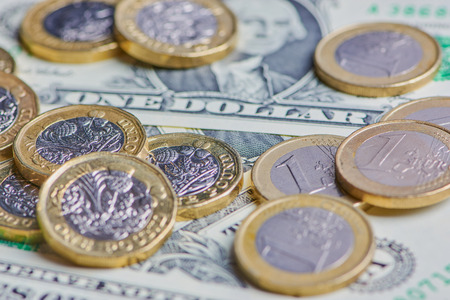 British Pound, Euro coins and US Dollar banknotes in a horizontal color macro picture Stock Photo