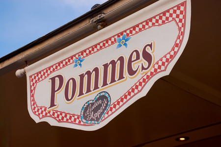 sign with the word Pommes which means chips in English and Enjoy your meal in German