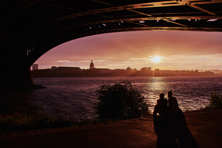 young couple is sitting during romantic sunset under the Theodor-Heuss bridge in Mainz, Germany Imagens