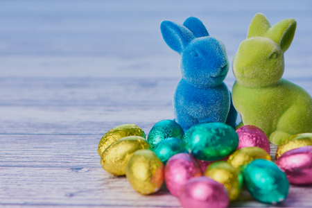 blue easter bunny and green easter bunny with wrapped chocolate eggs against white wooden background with copy space