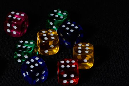 macro of eight colored dice with the figure six against black background