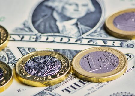 British Pound, Euro coins and US Dollar banknotes in a horizontal color macro picture Фото со стока