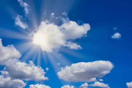sun is shining bright through white clouds on a blue sky, with sun rays 写真素材