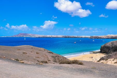 beach Playa de la Cera in Lanzarote, Spain with some hotels in the background and view to Playa Blanca