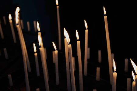 many long votive candles in a French church