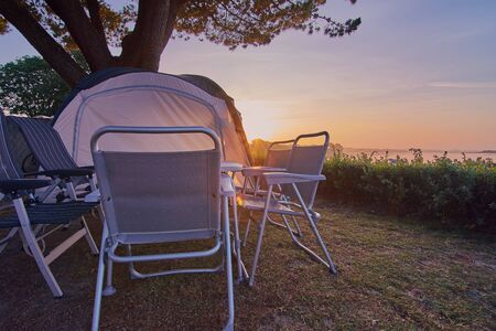 camping table with chairs and a tent standing on a campsite in front of a sunrise in France Stock fotó
