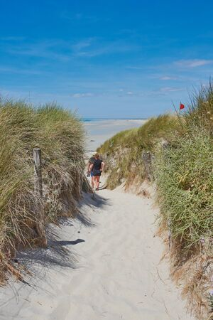 father and daughter are walking through the dunes at the surfer beach: la Torche