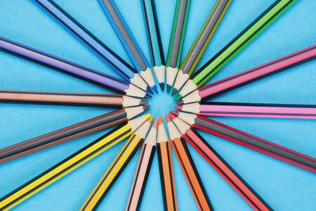 circle with a lot of different colored pencils on a blue background