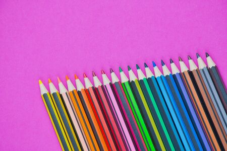 row of different colored pencils on a pink background with copy space