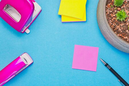 pink notepad with a pen on blue background beside pink punch and stapler, copy space