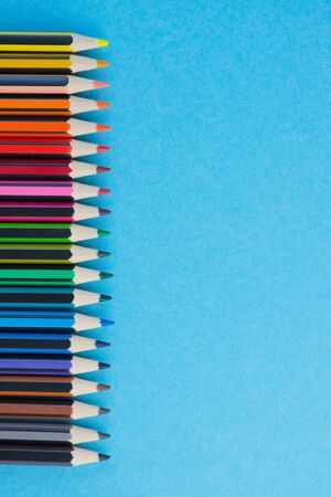 vertical photo of a row of colored pencils with different colors against light blue background, pencils on the left side with copy space