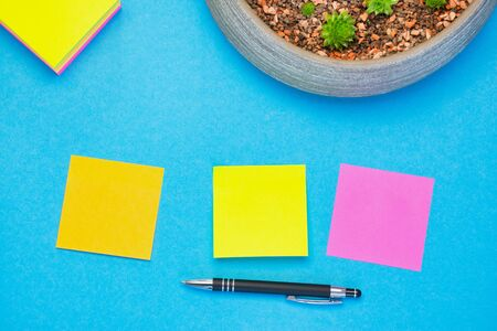 colored adhesive notes sticking on a blue background with a pen underneath with copy space