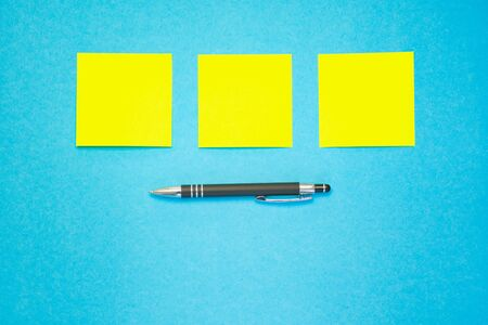 three yellow adhesive labels in a row over a pen against blue background, copy space Standard-Bild