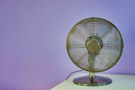 ventilator on a white table in front of a violet wall with copy space