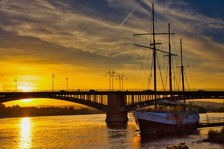 sunset at the Theodor-Heuss Bridge in Mainz-Kastel, Germany with a sailboat
