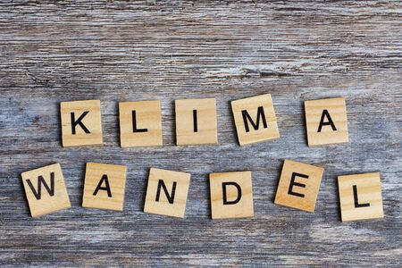 the German word means climate change in English, laid with wooden capital letters on wooden background