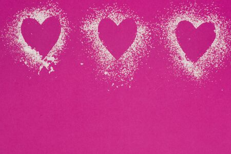 three powdered sugar hearts on pink background with copy space