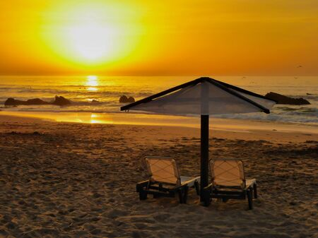 The famous beach called: Praia do Guincho in Portugal during sunset with sun chairs and a parasol