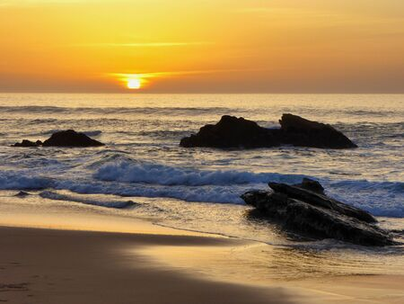 The famous beach called: Praia do Guincho in Portugal during sunset Banco de Imagens