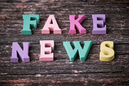 the English words - fake news - laid with wooden letters on wooden background