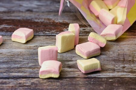 marshmallows lying in front of a colored bag on a wooden surface Stockfoto