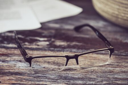 reading glasses lying on a wooden background