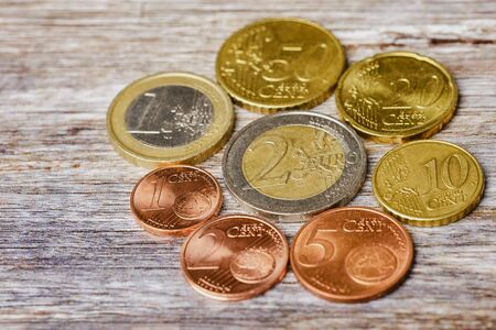 all the European coins lying in a circle on wooden background