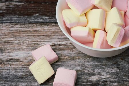 pink and yellow marshmallows in a white bowl on wooden surface, focus is on the sweets in the bowl Stockfoto