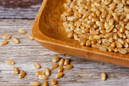 wheat grains in a wooden bowl on wooden surface