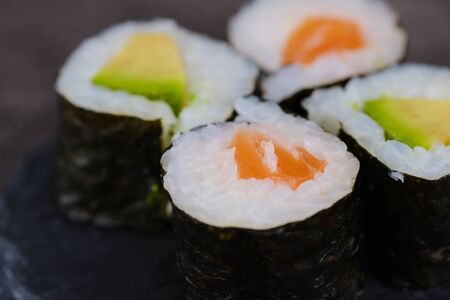 Sake maki Japanese roll with salmon and avocado, macro color photo