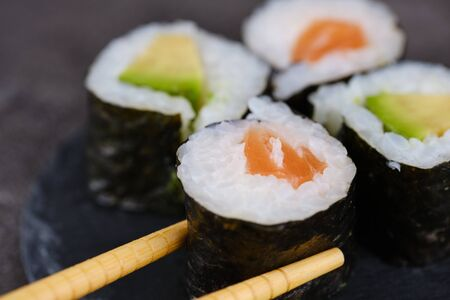 Sake maki Japanese roll with salmon and avocado, wooden chopsticks taking one roll Imagens