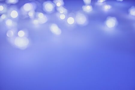 blurred color photo of a chain of lights as background picture in blue color with copy space