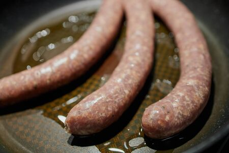 German raw bratwurst lying in fat in a pan Imagens