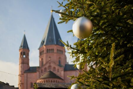 focus is on a christmas tree in the front, in the background is blurred the St. Martins cathedral of Mainz in  Germany