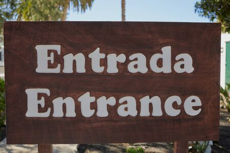 the Spanish and English word for -entrance- written on a big wooden sign