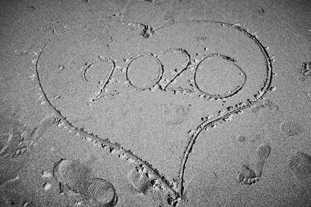 Heart shape in the sand on a beach with the year 2020 in it