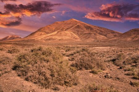 view to the volcanic mountain Hacha Grande near Papagayo beach in Lanzarote, Spain during sunset