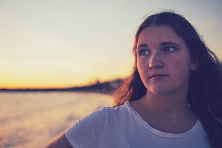 Teenage girl is looking thoughtful into the distance, in front of a sunset in Lanzarote