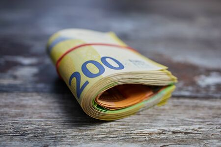 bundle of 200 Euro banknotes bound with household rubber on wooden surface