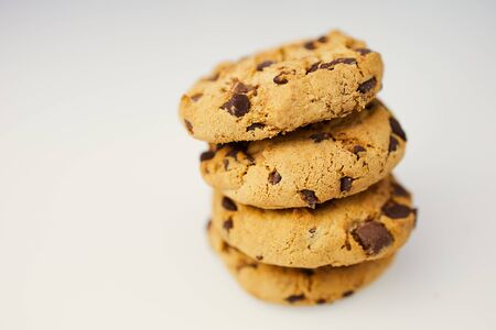 pile of chocolate cookies against white background with copy space