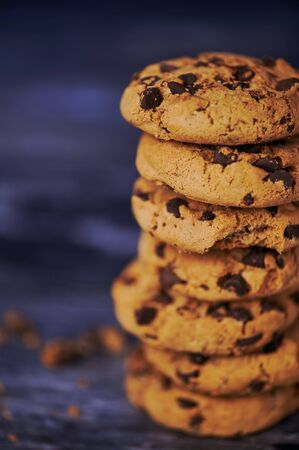 pile of chocolate cookies against wooden background with copy space, vertical macro photo Imagens