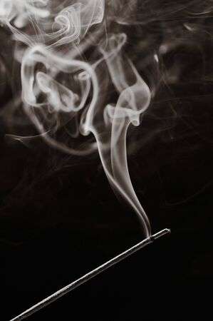 sepia toned black and white vertical  photo of a smoking incense stick