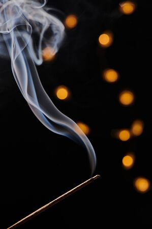 vertical macro photo of a smoking incense stick, in the background bokeh of a chain of lights