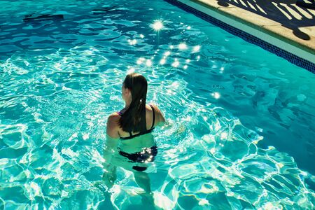 girl from behind standing in a swimming pool on a sunny day