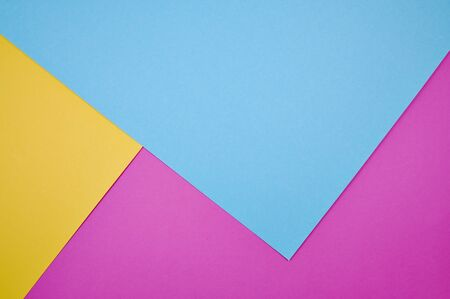magenta, yellow and blue colored papers laid together as background photo with copy space Imagens