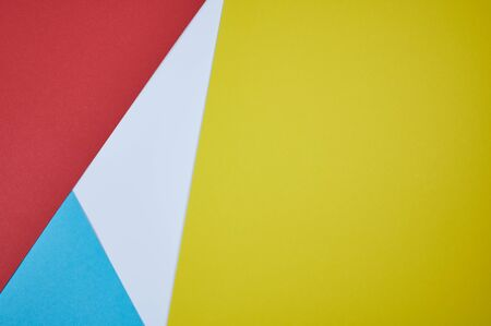 red, blue, white and yellow paper laid together in a pattern as photo background
