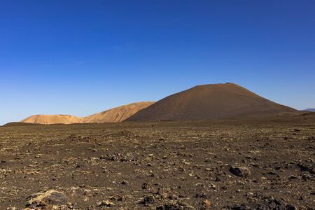 volcanic rocks near the Timanfaya National Park against cloudless blue sky in Lanzarote, Canary Islands