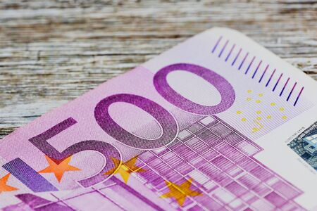 macro photo of five hundred Euro banknote against wooden brown background