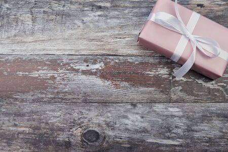one pink present in the right corner on wooden background