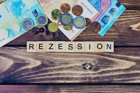 in the middle is lying the German word for recession, at the top Euro banknotes and coins, copy space Stock Photo